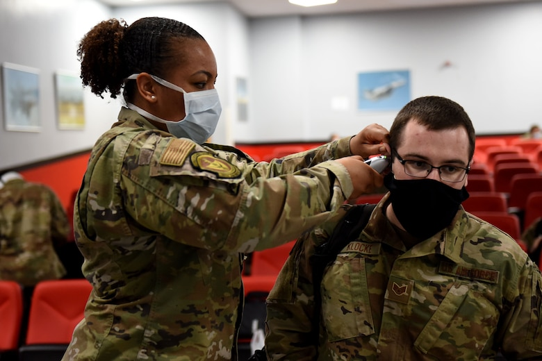 A 48th Medical Group Airman checks the temperature of an Airman assigned to the 492nd Fighter Squadron while completing pre-deployment line tasks at Royal Air Force Lakenheath, England, May 6, 2020. The 492nd FS is the first fighter squadron from the Liberty Wing to deploy since the start of the COVID-19 pandemic. (U.S. Air Force photo by Senior Airman Christopher S. Sparks)