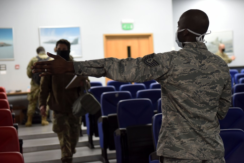 A 48th Fighter Wing Airman directs 492nd Fighter Squadron Airmen to their seats in effort to maintain social distancing during a pre-deployment processing line at Royal Air Force Lakenheath, England, May 6, 2020. The 492nd FS is the first fighter squadron from the Liberty Wing to deploy since the start of the COVID-19 pandemic. (U.S. Air Force photo by Senior Airman Christopher S. Sparks)