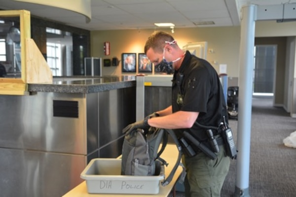 DIA Police Officer Scott Motes, wearing a protective face covering and gloves, inspects a bag while on-duty during the COVID-19 pandemic.