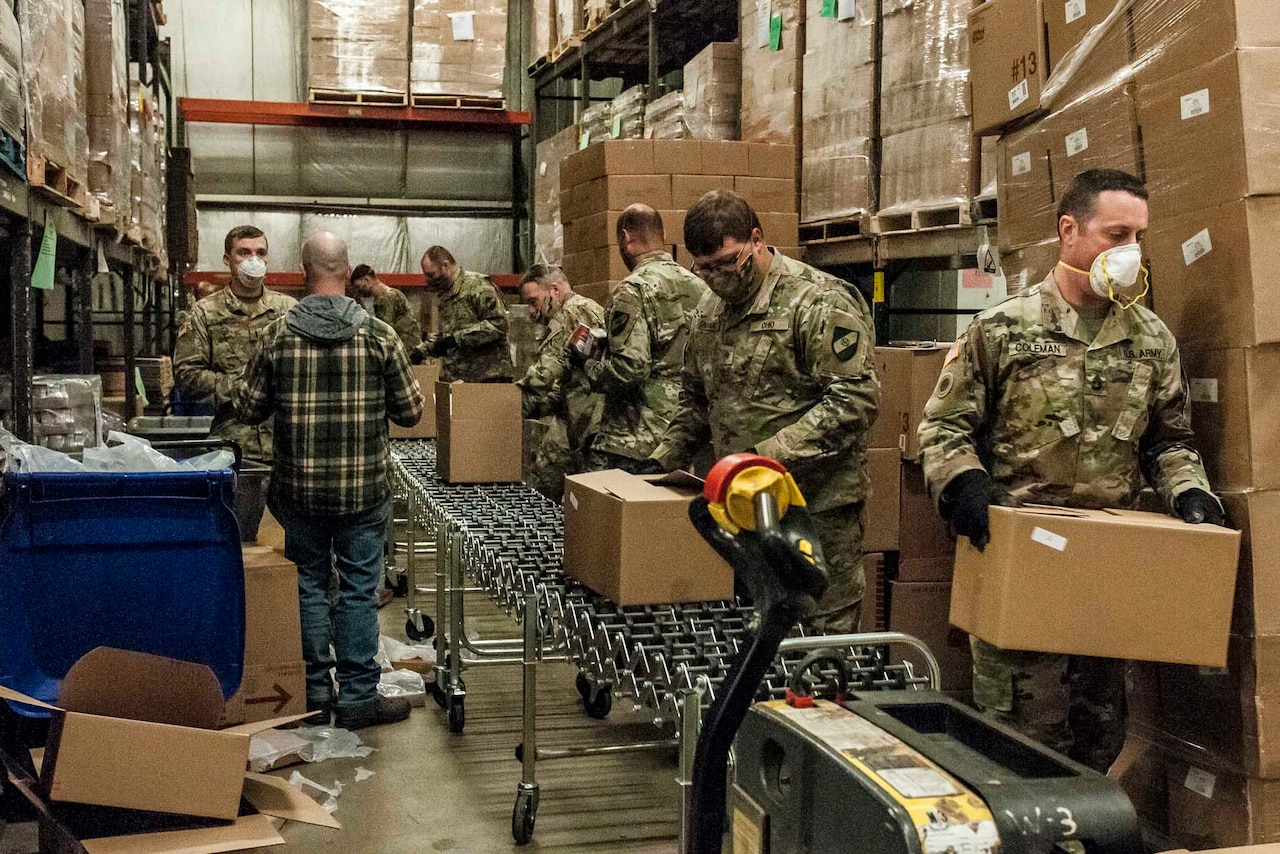 National Guardsmen preparing boxes of food.