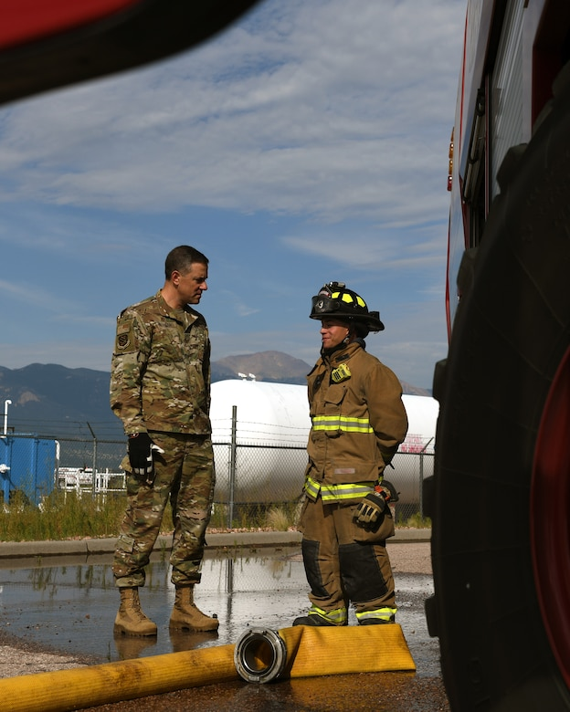 Col. Thomas Falzarano, 21st Space Wing commander, left, talks with Senior Airman Paul Karasiewicz, a 21st Civil Engineer Squadron firefighter Aug. 7, 2019, on Peterson Air Force Base, Colorado. Falzarano, as part of a tour of the 21st CES, met the many Airmen in the squadron and learned about what they do everyday. (U.S. Air Force photo by Airman 1st Class Andrew Bertain)