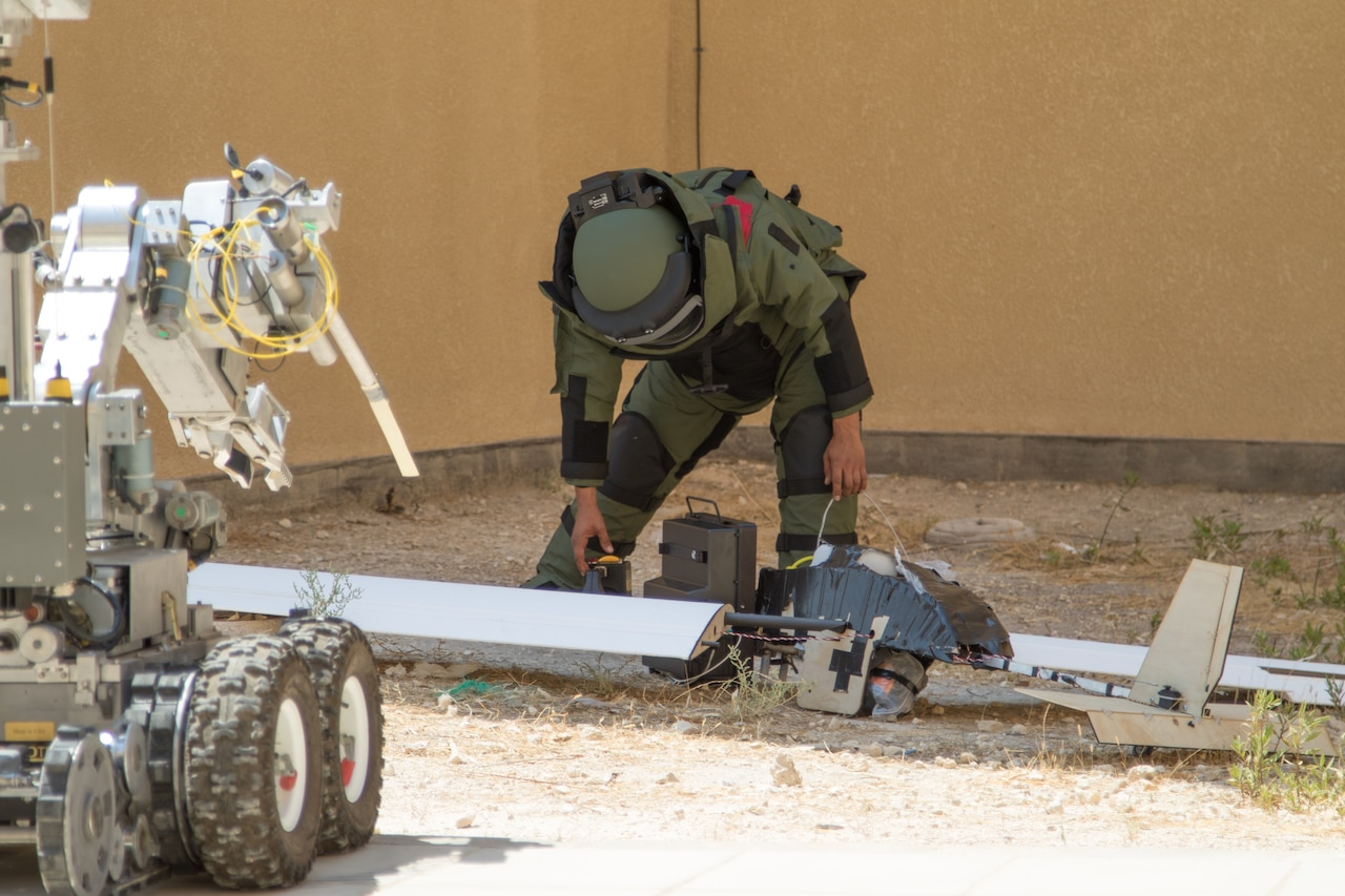 A soldier examines a simulated downed unmanned aerial vehicle during an exercise.