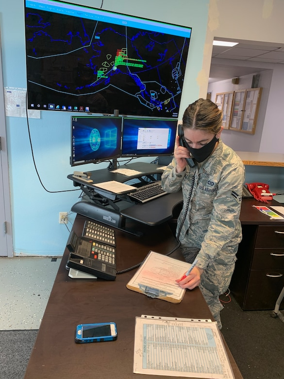 """U.S. Air Force Airman 1st Class Leandra Ventura-Perez, 3rd Operations Support Squadron Airfield Management operations coordinator, communicates with an aircrew while wearing a protective facemask at Joint Base Elmendorf-Richardson, Alaska, April 23, 2020. Amid the COVID-19 outbreak, the 3rd OSS Airfield Management team has been adopting a """"new normal"""" mentality as they operate in Health Protection Condition (HPCON) CHARLIE and incorporate protective measures to ensure the execution of JBER's essential flying missions."""
