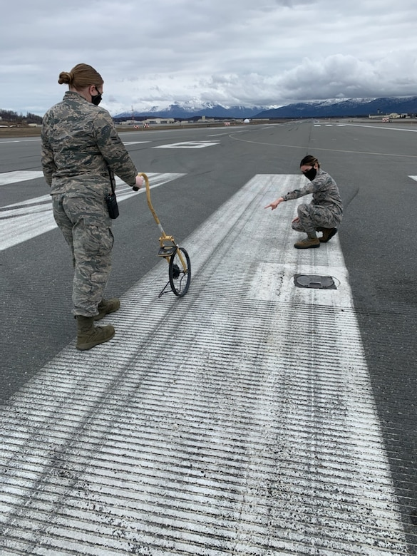 """U.S. Air Force Airmen 1st Class Hannah Klein and Leandra Ventura-Perez, 3rd Operations Support Squadron Airfield Management shift lead and operations coordinator, assess airfield pavement damage while wearing protective facemasks at Joint Base Elmendorf-Richardson, Alaska, April 23, 2020. Amid the COVID-19 outbreak, the 3rd OSS Airfield Management team has been adopting a """"new normal"""" mentality as they operate in Health Protection Condition (HPCON) CHARLIE and incorporate protective measures to ensure the execution of JBER's essential flying missions."""