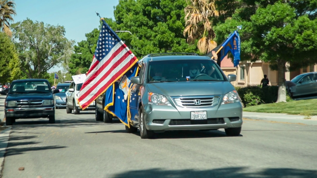 """A vehicle rolls down a neighborhood street during the """"Purple Up for Military Kids"""" car parade at Edwards Air Force Base, California, April 24. The parade was conducted to show appreciation and support for the base's children population. (Courtesy photo)"""