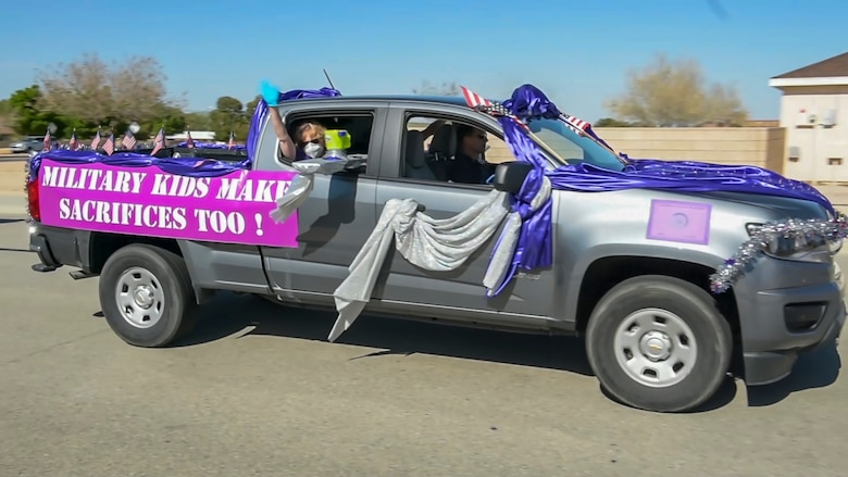 "A vehicle rolls down a neighborhood street during the ""Purple Up for Military Kids"" car parade at Edwards Air Force Base, California, April 24. The parade was conducted to show appreciation and support for the base's children population. (Courtesy photo)"