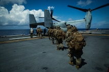 SOUTH CHINA SEA (April 21, 2020) Marines with Battalion Landing Team, 1st Battalion, 5th Marines, 31st Marine Expeditionary Unit (MEU), load onto an MV-22B Osprey tiltrotor aircraft with Marine Medium Tiltrotor Squadron (VMM) 265 (Reinforced), 31st Marine Expeditionary Unit (MEU), during a combat mission rehearsal aboard amphibious assault ship USS America (LHA 6). The Osprey is a long-range troop transport aircraft that can be deployed at a moment's notice, enabling the Blue-Green team to rapidly respond to crises. America, flagship of the America Expeditionary Strike Group, 31st MEU team, is operating in the U.S 7th Fleet area of operations to enhance interoperability with allies and partners and serve as a ready response force to defend peace and stability in the Indo-Pacific region. (Marine Corps photo by Sgt Audrey M. C. Rampton)