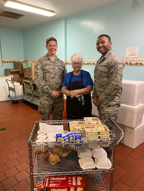 photo of two airmen and director of Okaloosa's Meals on Wheels pictured with food to be delivered to local seniors.