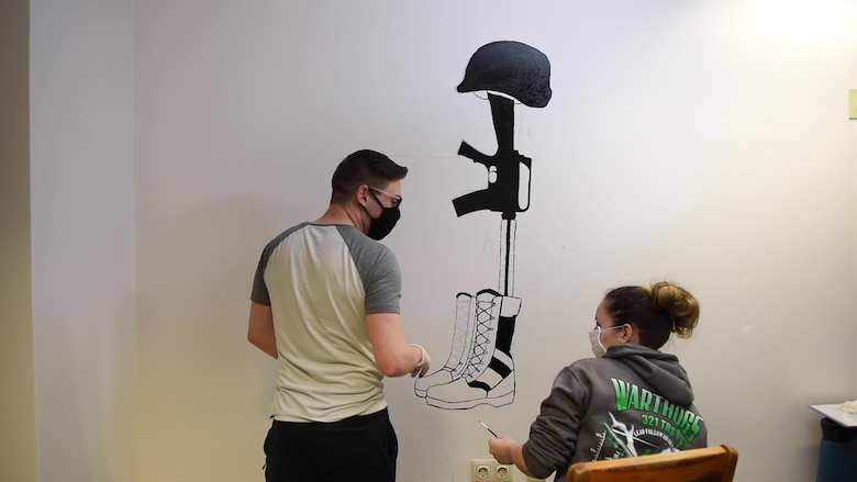 Photo of Airman painting a mural