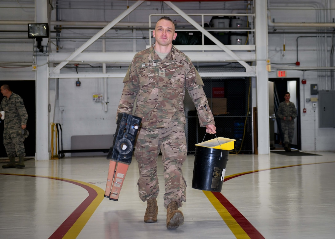 Staff Sgt. Brandon Miller, a heating, ventilation, air conditioning and refrigeration (HVACR) technician at the 910th Civil Engineer Squadron at YARS and Ohio State Highway Patrolman at the Ashtabula post in Ohio carries a few tools of his trade after completing a job in Hangar 305, Jan. 12, 2020.