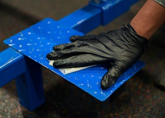 Airmen sanitize gym equipment