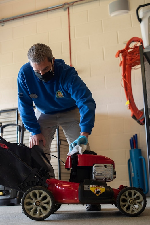 Keith Thomas, 100th Force Support Squadron Outdoor Recreation rental manager, sanitizes the top of a lawnmower inside the outdoor recreation center at RAF Mildenhall, England, May 11, 2020. To fight the spread of COVID-19, items returned from customers are thoroughly cleaned before being rented again. (U.S. Air Force photo by Airman 1st Class Joseph Barron)