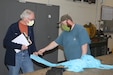 Logan Robinson, Letterkenny Army Depot (LEAD) (right), demonstrates an isolation gown prototype to James Eichelberger, WellSpan, at the LEAD upholstery shop on April 23, 2020. LEAD is currently producing personal protective equipment (PPE) for WellSpan to help combat COVID-19. (U.S. Army photo by Pam Goodhart)