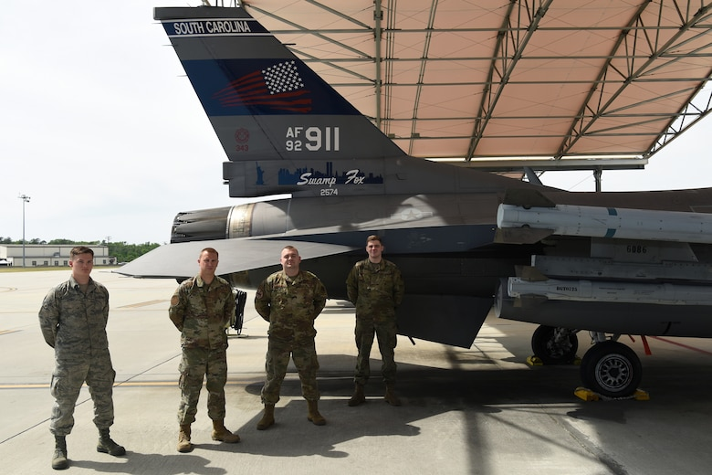 Pictured from left to right are Airman 1st Class Chase Szoke, Tech. Sgt. Austin Soltow, Staff Sgt. Michael Fisher and  Senior Airman Joseph Richter were part of a team who designed a commemorative tail flash on a Swamp Fox F-16 fighter jet with the tail number 911 to honor those who died during the terrorists attacks.