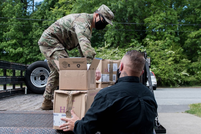 U.S. Army Staff Sgt. Nicolas Chang, 128th Aviation Brigade, Headquarters and Headquarters Company senior supply sergeant, and Josh Howe, Central Issue Facility supply technician, load boxes of face mask onto a truck at Joint Base Langley-Eustis, Virginia, May 13, 2020. The cost of each mask is $0.24 and 7.5 million were donated to the U.S. Army by a commercial vendor. (U.S. Air Force photo by Senior Airman Derek Seifert)