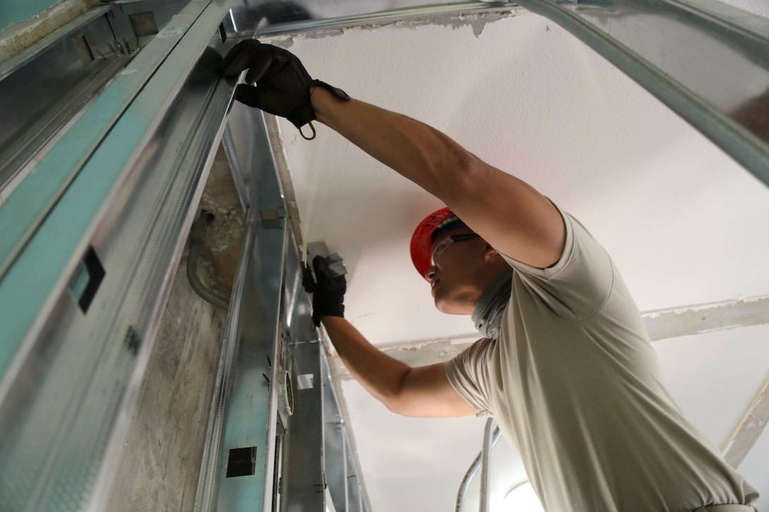 A National Guardsman works on a ceiling.