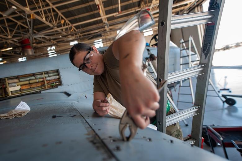 A photo of an Airman removing a bolt from an aircraft