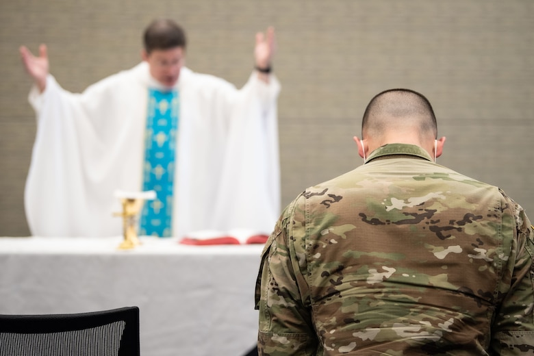 Chaplain holds hands in the air in front of alter next to Soldier with his head bowed