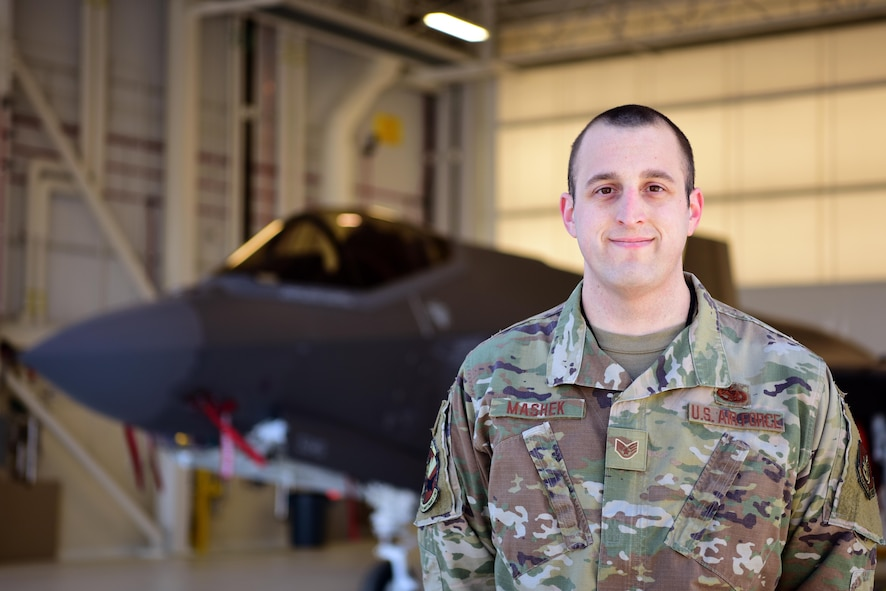 U.S. Air Force Staff Sgt. Christopher Mashek, a 356th Aircraft Maintenance Unit F-35A Lightning II crew chief, poses for a photo in front of an F-35A at Eielson Air Force Base, Alaska, May 1, 2020.