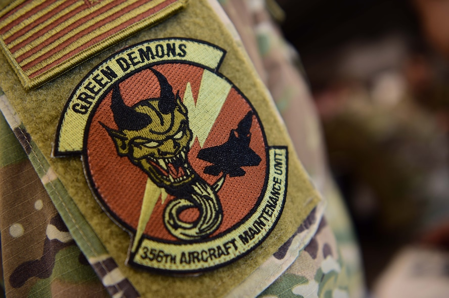 U.S. Air Force Staff Sgt. Christopher Mashek, a 356th Aircraft Maintenance Unit F-35A Lightning II crew chief, dons a Green Demons unit patch at Eielson Air Force Base, Alaska, May 1, 2020.