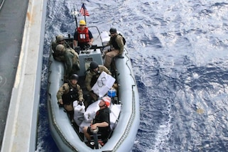 Military personnel in a boat alongside a ship.