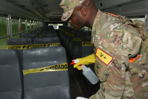 A Soldier disinfects a bus prior to AIT Graduates safely moving on to their first duty station.