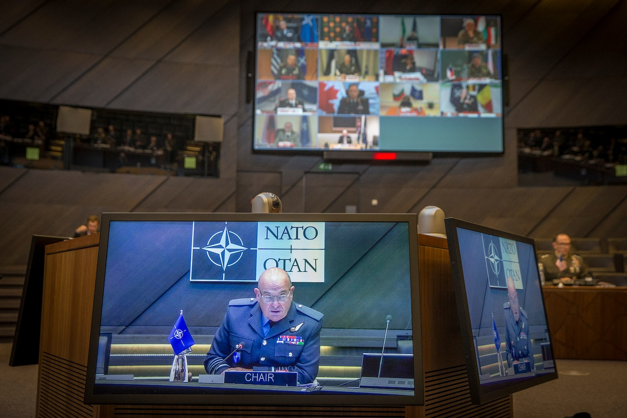 Multiple video monitors in a council room display men in military uniforms on a screen.