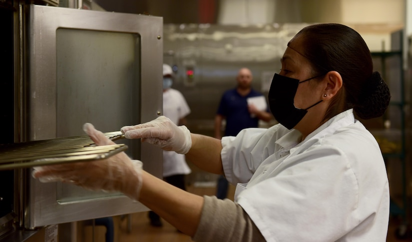 Patricia Munoz, Guardian Dining Facility (DFAC) food service worker, replaces oven racks after cleaning them at Creech Air Force Base, Nevada, April 17, 2020.