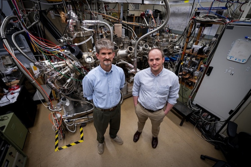 Two researchers pose in front a piece of research equipment.