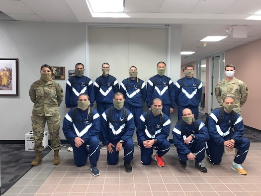 US Air Force Echo Flight trainees pose for a picture in the Commandant's hallway. Due to COVID-19 precautions, they are wearing facemasks as required. They had to stop by campus for  their placement exam before returning to the 737 TRSS learning lab for their classroom distance learning.