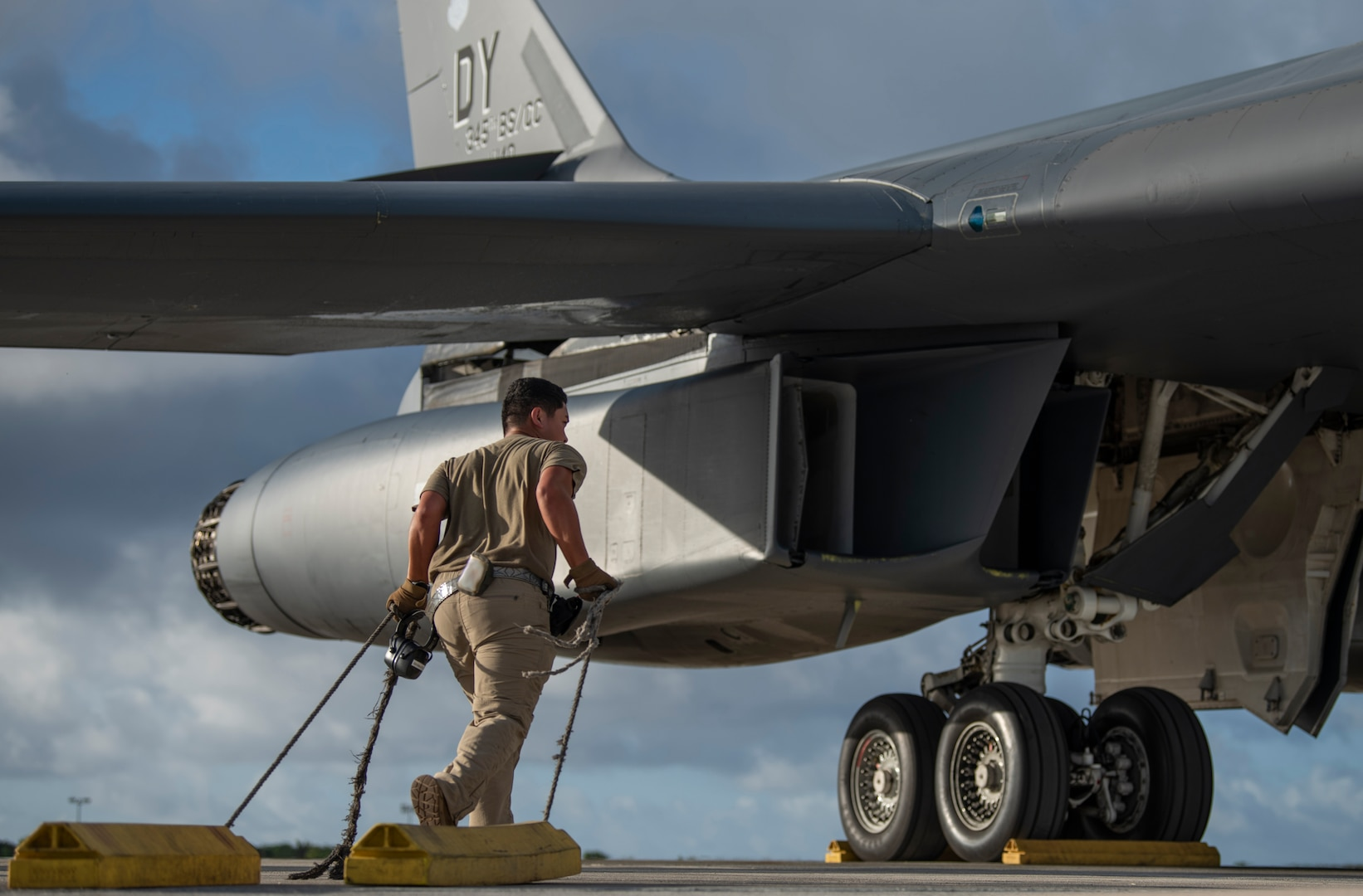 Senior Airman Jae Sajonas, 9th Expeditionary Bomb Squadron B-1B Lancer assistant crew chief, drags wheel chocks on the flightline at Andersen Air Force Base, Guam, May 14, 2020. Chocks prevent the aircraft from moving or swaying. Approximately 200 Airmen and four B-1s assigned to the 7th Bomb Wing at Dyess AFB, Texas, deployed to support Pacific Air Forces' training efforts with allies, partners and joint forces; and strategic deterrence missions. (U.S. Air Force photo illustration by Senior Airman River Bruce)