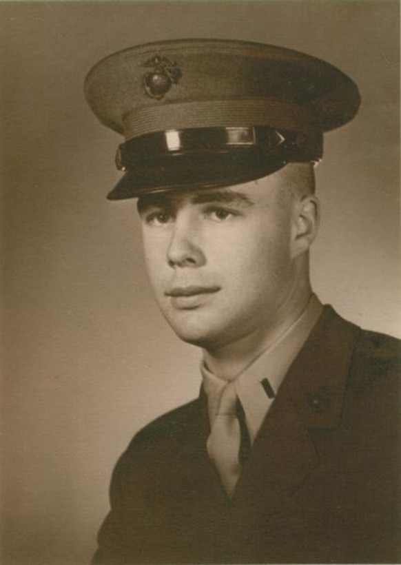 A man in a military hat and uniform poses for an official photo.