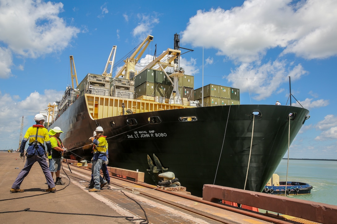 Four men pull on a cable attached to a massive container ship at port.