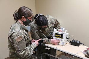 U.S. Air Force Senior Airman Marissa Cerra (right) practices checking an incoming patient for fever and abnormal health while conducting drills prior to accepting live patients, at the North Carolina National Guard Medical Support Shelter (MSS), Central North Carolina, April 29, 2020. The MSS is intended to act as an overflow shelter for hospital patients not infected with the COVID-19 virus and is maned by a joint task force of Army and Airforce National Guard medical staff.