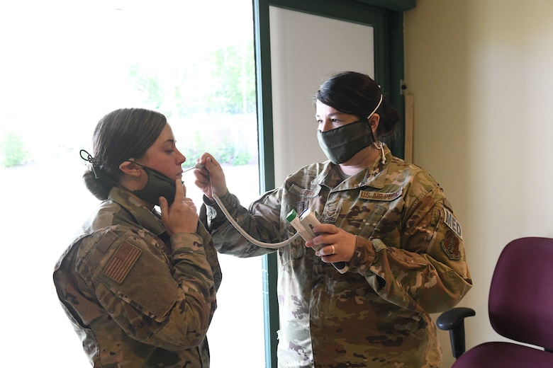 U.S. Air Force Senior Airman Marissa Cerra (right) practices checking an incoming patient for fever and abnormal health while conducting drills prior to accepting live patients, at the North Carolina National Guard Medical Support Shelter (MSS), Central North Carolina, April 29, 2020. TThe MSS is intended to act as an overflow shelter for hospital patients not infected with the COVID-19 virus and is maned by a joint task force of Army and Airforce National Guard medical staff.