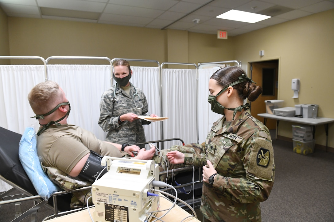 U.S. Air Force Capt. Lauri Bailey, a registered nurse for the 145th Medical Group (left) and U.S. Army Specialist Samantha Klimczak, a medic with the North Carolina Army National Guard (right) practice treating a simulated patient, while conducting drills prior to the arrival of live patients, at the North Carolina National Guard Medical Support Shelter (MSS), Central North Carolina, April 29, 2020. The MSS is intended to act as an overflow shelter for hospital patients not infected with the COVID-19 virus and is maned by a joint task force of Army and Airforce National Guard medical staff.