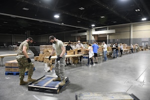 Members of the 145th Airlift Wing assist the Charlotte Metrolina Food Bank by helping to transport supplies and box food packages for North Carolina citizens in need.