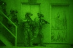 As seen through night-vision goggles, Air Force special tactics airmen prepare to enter a building in search of a high-value individual during exercise Southern Strike 2020 at Camp McCain Training Center, Miss., Feb. 3, 2020. Southern Strike is a large-scale, joint and international combat exercise, featuring counterinsurgency, close air support, en route casualty care, noncombatant evacuation and maritime special operations.