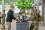 Soldiers wash their hands and social distance.
