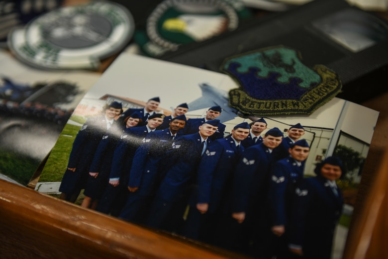 A picture of class 99-A Aviano Airman Leadership School, from a time capsule, is displayed with a wyvern patch and videotape at Aviano Air Base, Italy, May 15, 2020. The class was made up of two flights with a total of 23 students. (U.S. Air Force photo by Airman 1st Class Ericka A. Woolever)