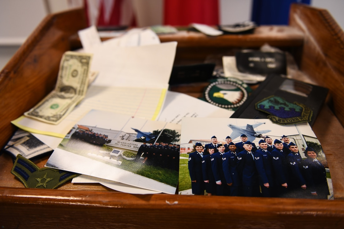 Various items are displayed on top of a time capsule at Aviano Air Base, Italy, May 15, 2020. The 31st Logistics Readiness Squadron found the time capsules constructed by the class of 99-A Aviano Airman Leadership School. (U.S. Air Force photo by Airman 1st Class Ericka A. Woolever)