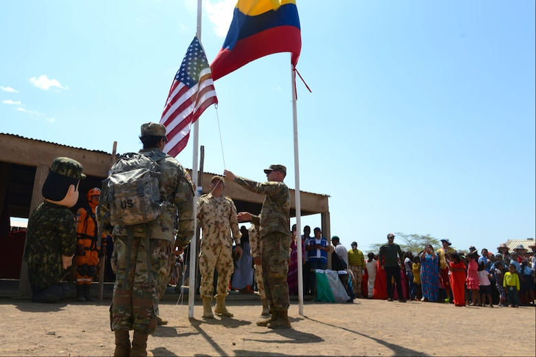 Participants at a medical readiness exercise raise an American flag owned by Chief Warrant Officer 4 Joval Eblen III alongside the flag of Colombia during Exercise Vita in Tres Bocas, La Guajira, Colombia March 12, 2020.