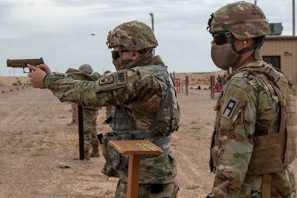 Spc. Henry Jacob, a military police Soldier assigned to 253 Military Police Company, Tennessee National Guard, fires an M17 pistol at McGregor Range Complex, New Mexico, May 10, 2020, while Sgt. Zachary Yarbrough, right, an observer coach/trainer assigned to 2-340 Training Support Battalion, 5th Armored Brigade, watches.
