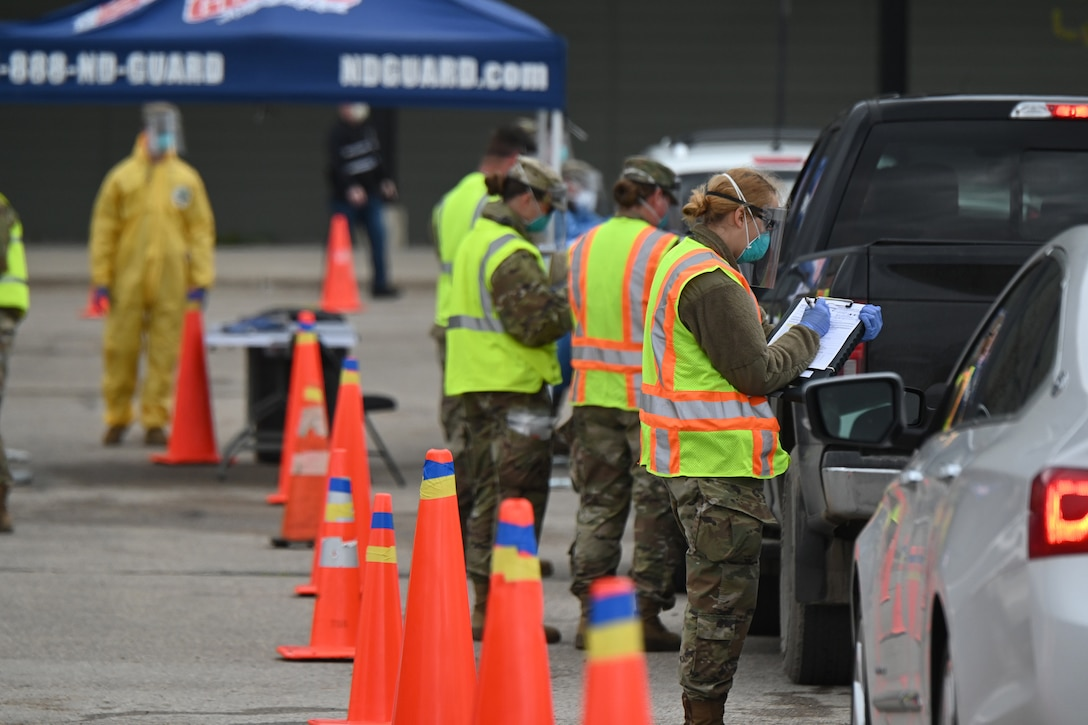 Photo of N.D. National Guard personnel dressed in personal protective equipment as the provide voluntary COVID-19 tests for community members lined up in their cars in the parking lot of the Alerus Center parking lot, Grand Forks, N.D., may 14, 2020.
