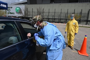 Photo of two National Guard members dressed in personal protective equipment as they take a voluntary COVID-19 test for a community member stopped in a car in the parking of the Alerus Center, Grand Forks, N.D., May 14, 2020.