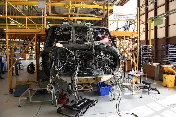 Mary King, aircraft electrician in the avionics/electrical branch at the Corpus Christi Army Depot, Texas, installs the instrument panel wiring harness as part of the assembly and repair of the UH-60L to UH-60V upgrade.(U.S. Army photo by Ervey Martinez)