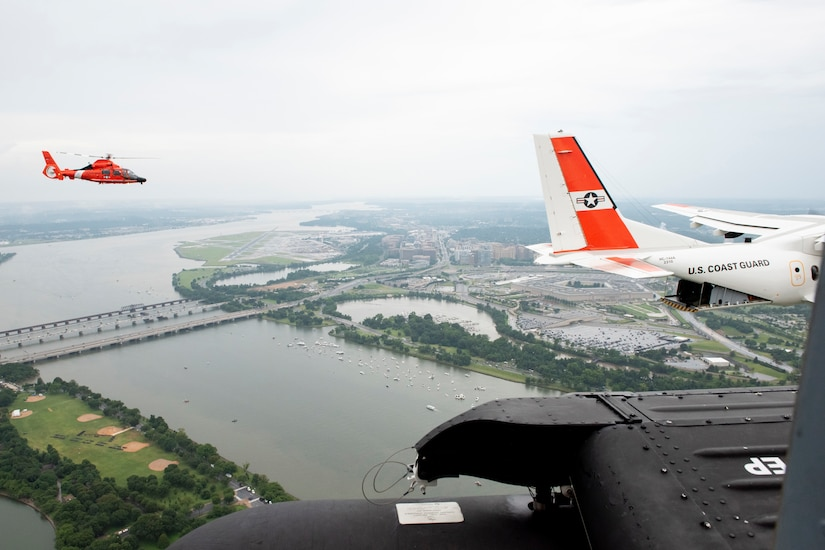 Aircraft fly over a large river and city.