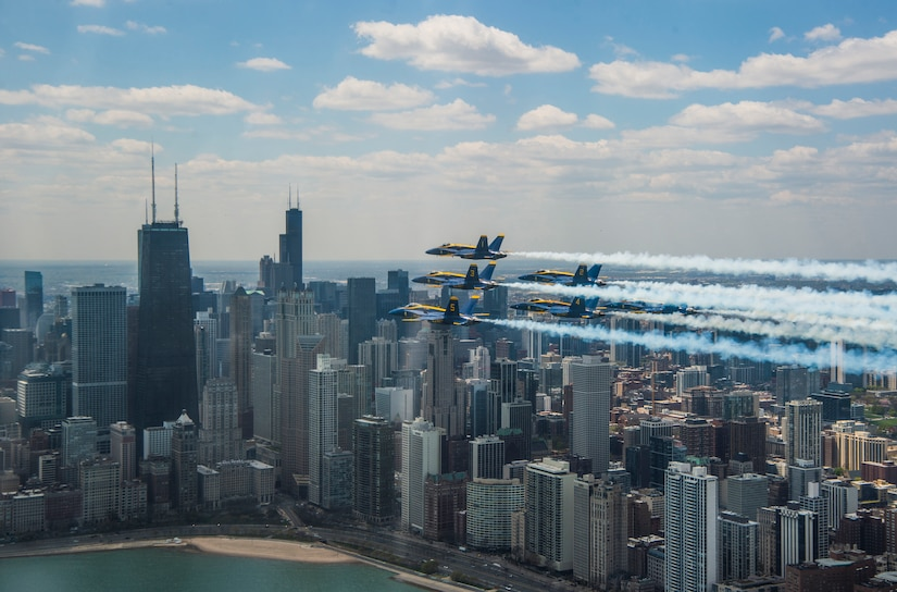Jets fly over a city with many tall buildings.