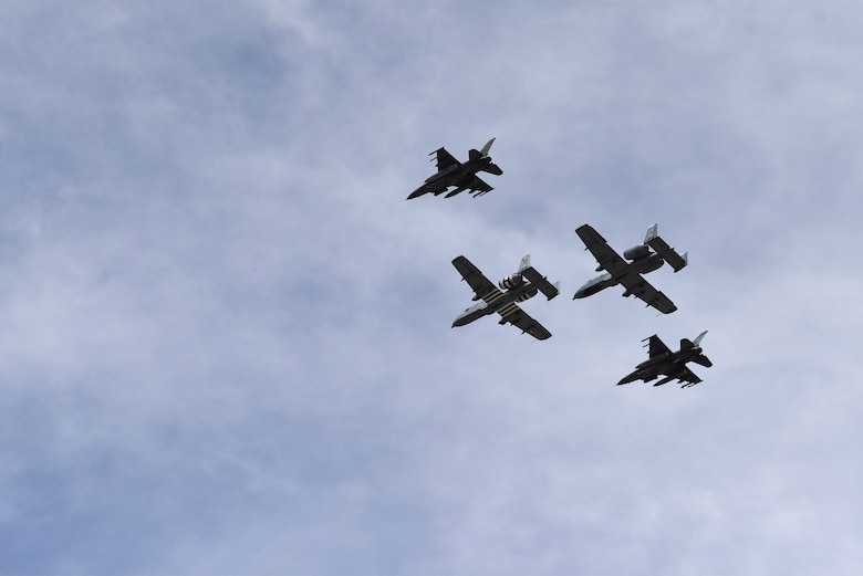 A photo a four-ship formation performing a flyover.