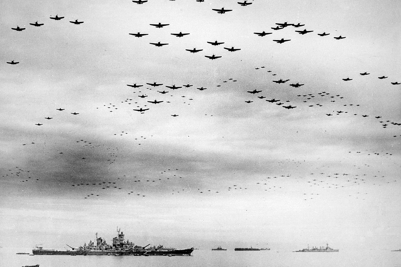 Hundreds of World War II-era aircraft fly over a large ship.